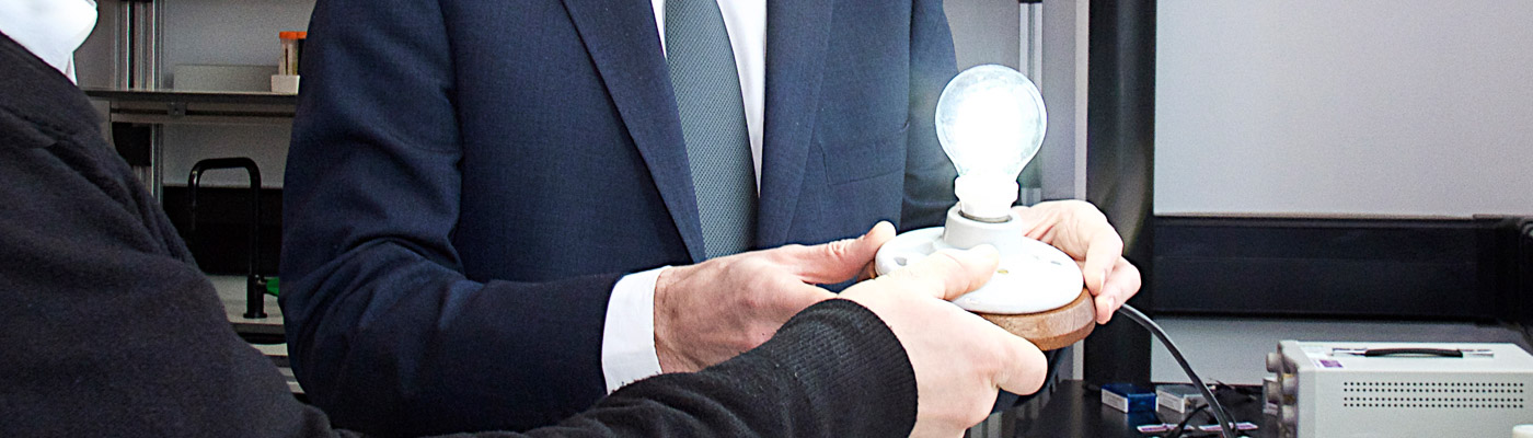 two people holding a graphene lightbulb