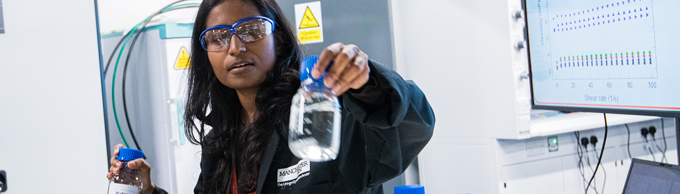 Female researcher showing a sample bottle containing graphene in solution