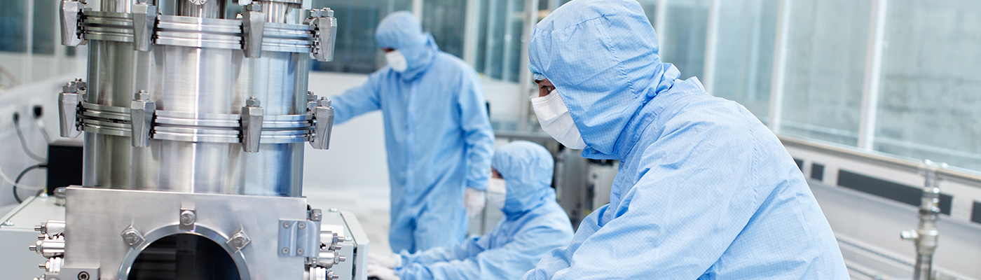 Three researchers working in a clean room laboratory